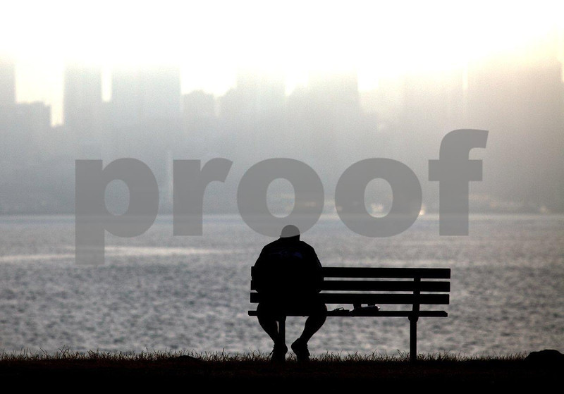 Man sitting on bench enjoys his newspaper and coffee with the Seattle skyline emerging from the moring fog.