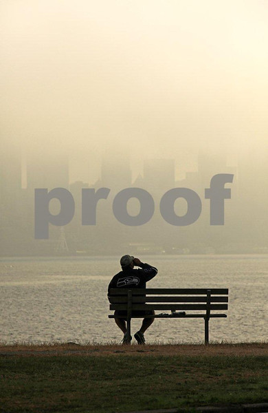 Man sitting on a bench enjoys his newspaper and coffee with the Seattle skyline emerging from the morning fog. Look closely for the Seahawks jacket.