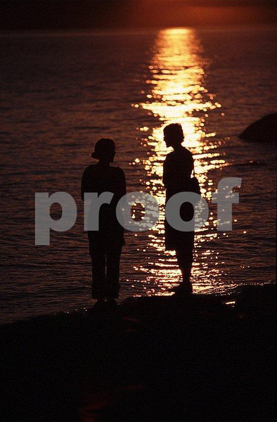 Two girls standing near the beach at sunset.