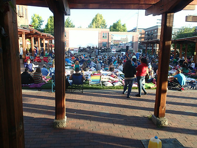 Crowds gather early for the outdoor movie night at the local square.