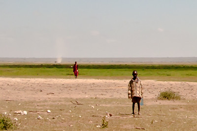 Maasi man in traditional dress is flanked by a young boy in his western coat in the foreground, and in the background a whirlwind. The past, the present, and the winds of change that travel across the African Continent.