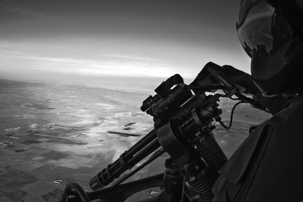 a UH-1Y Aerial Observer mans a GAU-17 Minigun over Afghanistan