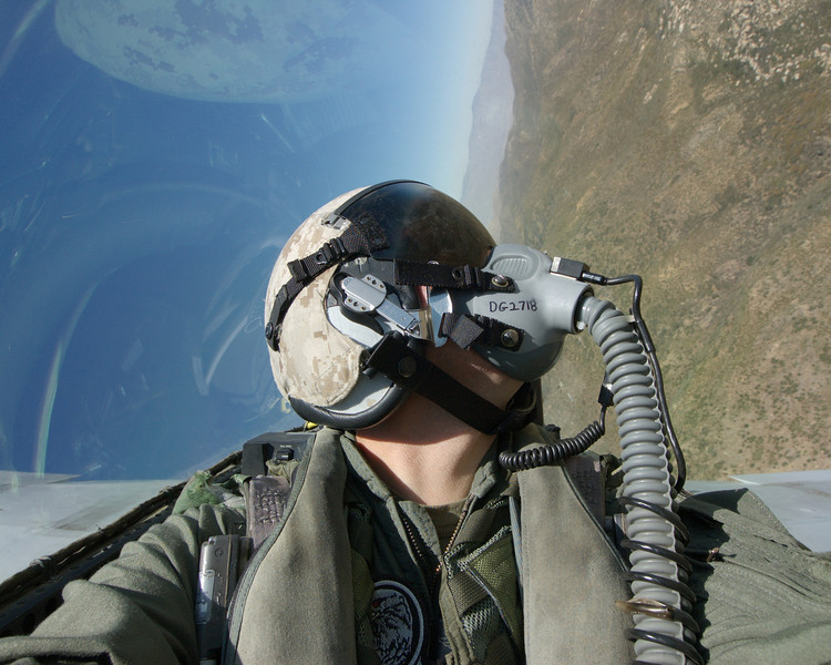 F/A-18D Weapons and Sensors Officer (WSO) clears the terrain below his aircraft during a low-level flight.