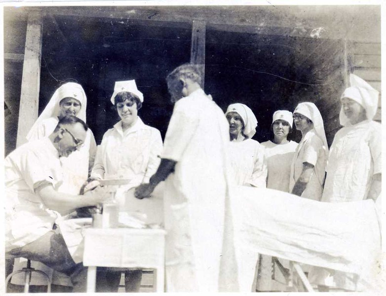 Red cross workers performing medical treatment outside (08488)