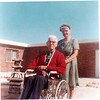Mrs. Akers Pushing Dr. Akers' Wheelchair Outside, Feb 1969 (08482)