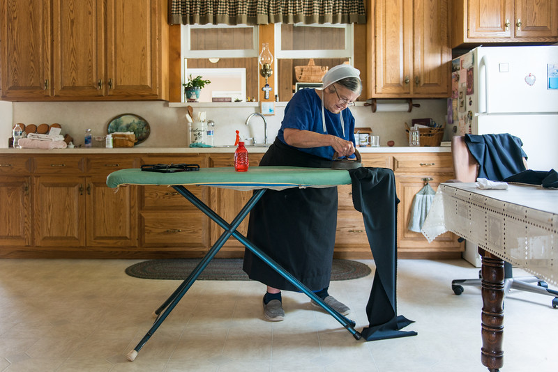 Amish Lady Ironing In Kitchen