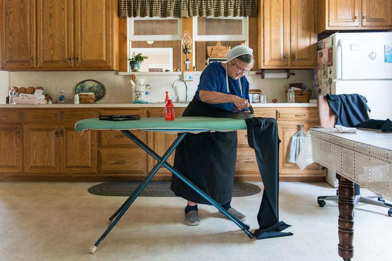 Amish Lady Ironing In Kitchen