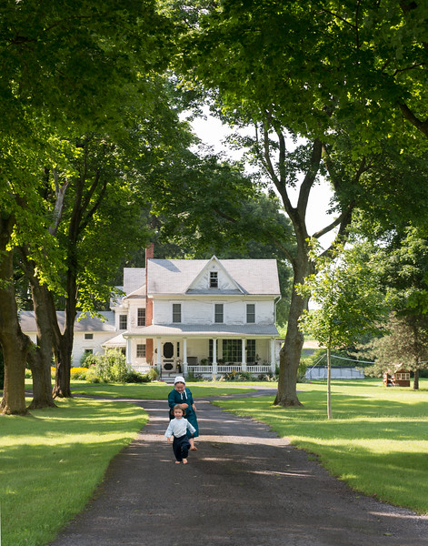 Amish children playing in front of historic house