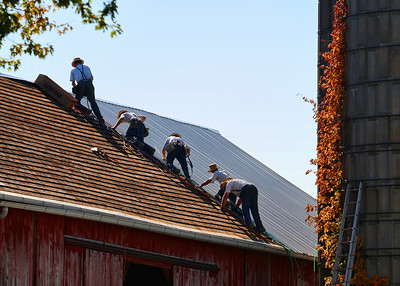 Amish men roofing a barn