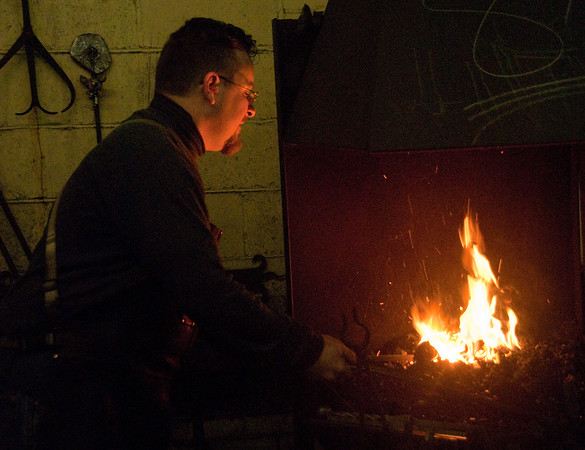"""In almost every film and novel, the village blacksmith is a massive man who uses brute strength and sheer will-power to pound, flex and bend red-hot metal into whatever is needed.  When I went to the large warehouse-size forge of <a href=""""http://www.artisansoftheanvil.com/""""target=""""_blank"""">Artisans of the Anvil</a> , I discovered three men -- Andrew Molinaro, Josh Blum and Rich Prevost -- who didn't so much defy the stereotype as refine it, forging the role of blacksmith into something very personal, creative and precise.    Here, Andrew, the master of the shop, tends one of the forge fires. Later that day, he had me try my hand at blacksmithing, explaining how he judges the heat of the fire and of any metal he puts into it, by color. He instructed me to be sure to place the metal rod at just the right place within the flames, for maximum heat. But to be very careful to not let the metal burn."""