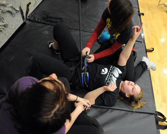 "Ashley Murphygets help from her friends, Kristina Bleeker, bottom, and Kaitlynne Pratt, after finishing her climb in class.<br /> Ashley Murphy, a senior at Erie High School, falls under the McKinney Vento Act for ""homeless"" students because she lives with her boyfriend's parents (living with someone who is not a legal guardian).<br /> For more photos and a video of Murphy, go to  <a href=""http://www.dailycamera.com"">http://www.dailycamera.com</a><br /> Cliff Grassmick / November 17, 2011"