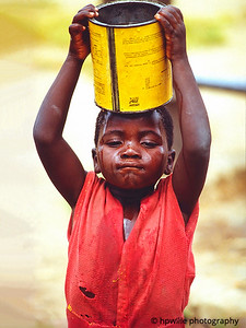 Little girl bringing drinking water to family.