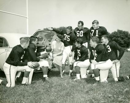 Bill Dudley #35, and 7 UVA players in uniform next to a young lady seated at an open trunk of a car full of footballs (02672)