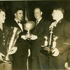 Bill Dudley in army uniform holding a trophy, three other gentleman in the photo in suits at the Washington Touchdown Club gathering in 1945 (02663)