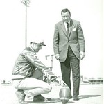 Bill Dudley standing over a man holding a ball in place (02507)
