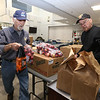 Billerica Senior Center volunteers Art Collier, 88, left, and Joe Duggan, 82, both of Billerica, help move food from the food bank for a monthly delivery, before they set up the tables and chairs for weekly Bingo at the Senior Center.  (SUN/Julia Malakie)
