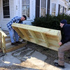 Billerica firefighters install a wheelchair ramp for Talbot Ave resident Chris Clark, 34, who has multiple sclerosis and uses a walker. Chuck McDevitt, left, and Dave Forziati, lift the platform for the porch into place. (SUN/Julia Malakie)