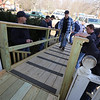 Billerica firefighters install a wheelchair ramp for Talbot Ave resident Chris Clark, 34, who has multiple sclerosis and uses a walker. Firefighter Chuck McDevitt jumps up and down on the ramp to see if it's stable.  (SUN/Julia Malakie)