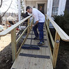 Billerica firefighters install a wheelchair ramp for Talbot Ave resident Chris Clark, 34, who has multiple sclerosis and uses a walker. Dispatcher John Pellegrino sweeps the ramp as Clark watches from the doorway. (SUN/Julia Malakie)