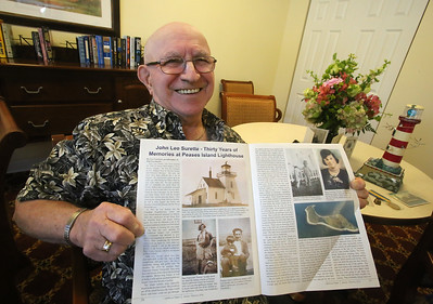 Joseph Surette, 84, of Billerica with article in Lighthouse Digest about his father, Jean Leo Surette, who was lighthouse keeper on tiny Pease Island in Nova Scotia from 1921-1952. The family will attend a plaque dedication at the Wedgeport Museum in Nova Scotia on April 8.  (SUN/Julia Malakie)