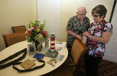 Joseph Surette, 84, of Billerica, and daughter Lisa Courtenay, also of Billerica, call two of Joseph's sisters in Nova Scotia. On table are mementos of Joseph's dad, Jean Leo Surette, who was in WWI and then was lighthouse keeper on tiny Pease Island in Nova Scotia from 1921-1952. The family will attend a plaque dedication at the Wedgeport Museum in Nova Scotia on April 8.  (SUN/Julia Malakie)