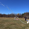 Warllon Silva of Dracut flies his Brazilian fighter kite, with his fiancee Haley Montbleau and daughter Kara Silva, 2-1/2, at an almost-empty Regatta Field Wednesday afternoon.(SUN/Julia Malakie)