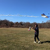 Warllon Silva of Dracut flies his Brazilian fighter kite, with his fiancee Haley Montbleau and daughter Kara Silva, 2-1/2, rear, at an almost-empty Regatta Field Wednesday afternoon.(SUN/Julia Malakie)