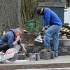 William Donohue, left, and helper Brian [who didn't want to give last name], both of Brighton, build a retaining wall for a front yard on Treble Cove Road in Billerica, using colonial retaining wall blocks. What they've finished is about three days' work.  JULIA MALAKIE/LOWELLSUN