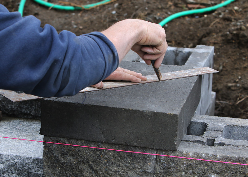 William Donohue of Brighton scores a block to cut for a mitered corner for the top of the wall as he builds a retaining wall for a front yard on Treble Cove Road in Billerica, using colonial retaining wall blocks. What they've finished is about three days' work.  JULIA MALAKIE/LOWELLSUN