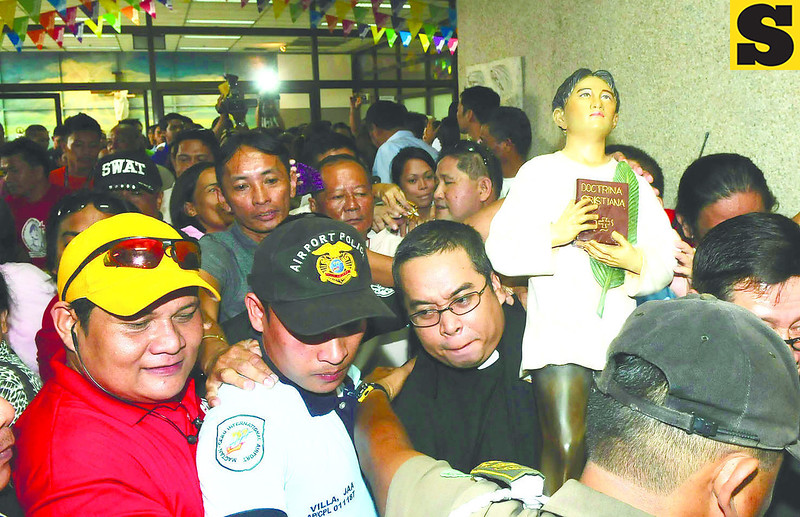 BEFORE HE LEAVES.  Rev. Fr. Charles Louis Jayme (in black, foreground) carries the official image of Blessed Pedro Calungsod, as devotees reach out to touch the figure at the Mactan-Cebu International Airport. (Arni Aclao)