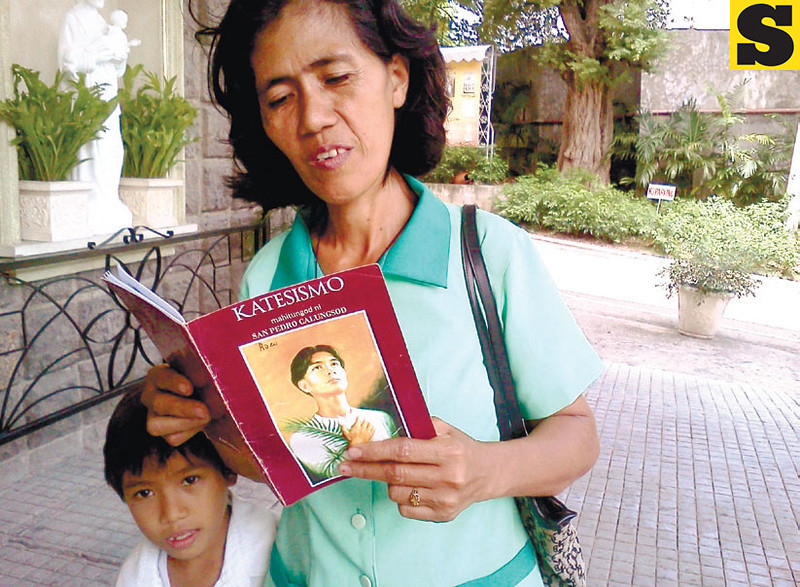 "BELIEVER. Rosario Polinar Melecio, 46, opens the catechism guide on Pedro Calungsod while sharing the ""miracle"" she experienced through his intercession. Her youngest child accompanies her outside the Archdiocesan Shrine of Blessed Pedro Calungsod on D. Jakosalem St., Cebu City. (Sun.Star Photo/Kevin A. Lagunda)"