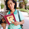 """BELIEVER.Rosario Polinar Melecio, 46, opens the catechism guide on Pedro Calungsod while sharing the """"miracle"""" she experienced through his intercession. Her youngest child accompanies her outside the Archdiocesan Shrine of Blessed Pedro Calungsod on D. Jakosalem St., Cebu City. (Sun.Star Photo/Kevin A. Lagunda)"""