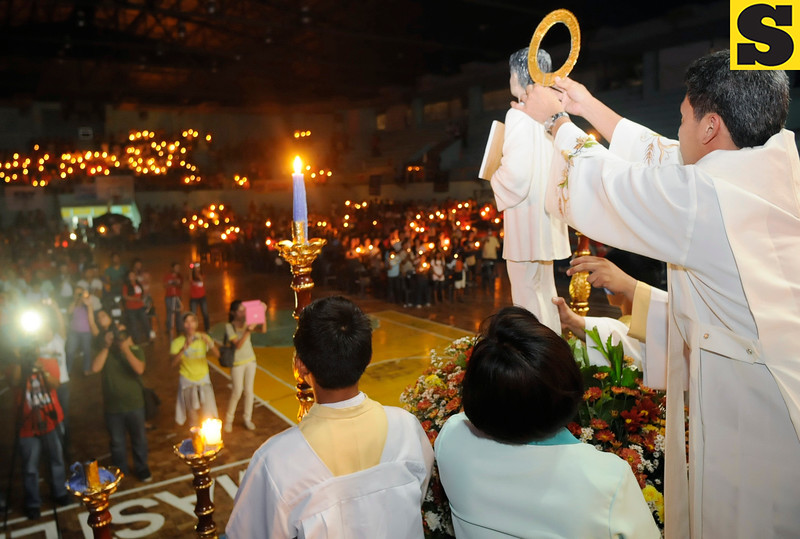 THE HALO EFFECT.  In the Mandaue City Sports and Cultural Complex, Rev. Fr. Randy Nebrea places the halo on an image of St. Pedro Calungsod, right after a live stream from the Vatican shows the rite of canonization. Hundreds of catechists and parishioners, many of them young, attended the candle-lit celebration. (Sun.Star Photo/Allan Cuizon)