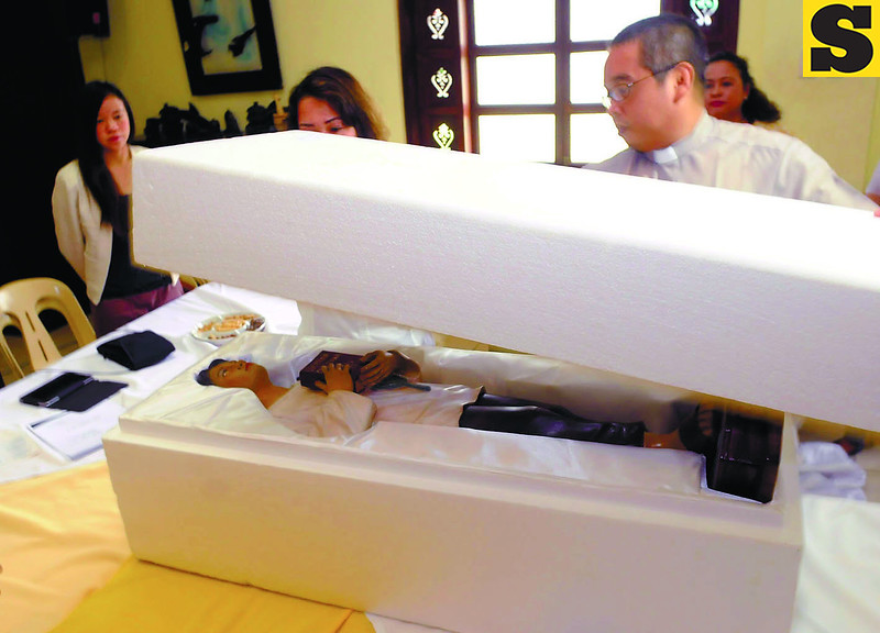OFF TO ROME. Rev. Fr. Charles Louis Jayme places the lid on the box of the image of Blessed Pedro Calungsod for its trip to Rome for the canonization rites. The demonstration was part of a press conference at the Archbishop's Residence. (Sun.Star/Arni Aclao)
