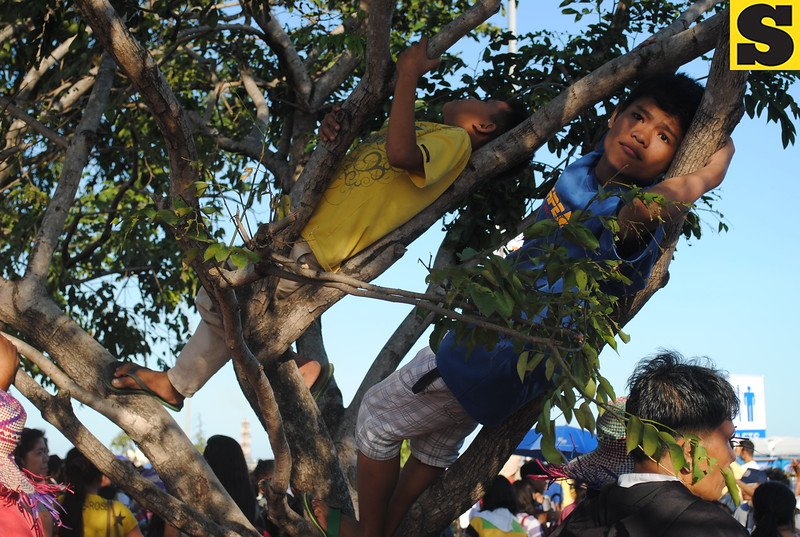While their parents are busy preparing for the arrival of Galleon San Diego, these kids are resting on a tree. (Nera Mariz Puyo/USJR MassComm Intern)