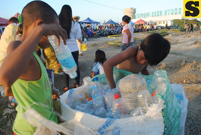 Kids collect empty plastic bottles littered at the thanksgiving mass site. One of them said 16 bottles are equivalent to 10 pesos. They will use the money to buy food and pay school fees. (Jolina Ylaya/USJR MassComm Intern)
