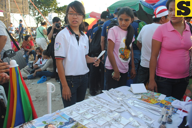 Student volunteers from Dalubhasaan Ng Lungsod Ng San Pablo (DLSP), Laguna, sell shirts,stampitas, comics and other San Pedro Calungsod memorabilia. They are set to go back to Laguna on Monday. (Nera Mariz Puyo/USJR MassComm Intern)
