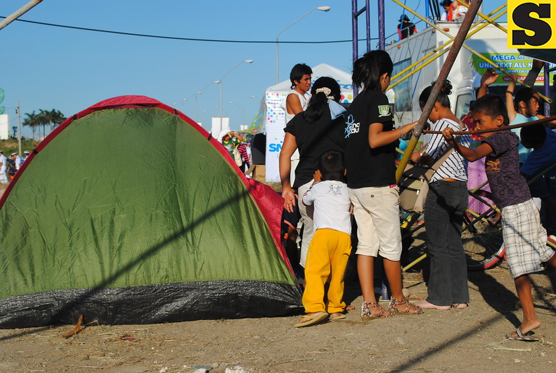 A family busily prepares a tent for shelter at the site of the Thanksgiving mass. (Nera Mariz Puyo/USJR MassComm Intern)