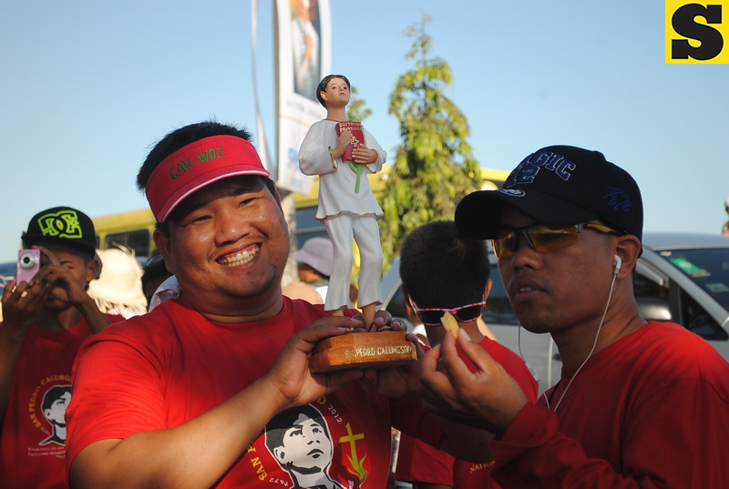 Mandaue City Councilor Wilmer Zanoria raises the image of San Pedro Calungsod. Zanoria, together with his wife Adele and the rest of the family, participated in the whole procession. (Nera Mariz Puyo/USJR MassComm Intern)