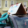 Car caravan of Lowell Community Health Center employees gathers at the Mooday Elementary School and drives by the Pleasant Street home of medical assistant Hilda Bettencourt, who just retired after 41-1/2 years at LCHC. Nurse practitioner Rebecca Chase of Wilmington, left, helps pediatrician Katie Bonacci of Belmont with a sign. (SUN/Julia Malakie)