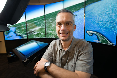 Carsten Braun, Professor of Geography & Regional Planning at Westfield State University, in front of the Google Liquid Galaxy display in the Ely Library