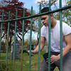 St. Patrick's Cemetery groundskeeper Aaron Diaz of Lowell repaints the fence along Gorham Street, which he said needs painting every two or three years, and this year it's his turn. (SUN/Julia Malakie)