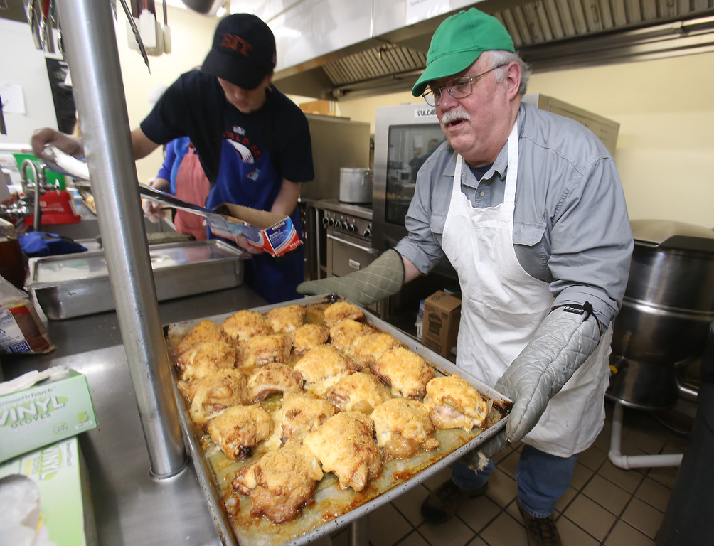 . Table of Plenty volunteers prepare meal at Chelmsford Senior Center. Paul Windt of Chelmsford moves trays of Parmesan Crusted Chicken just out of the oven. At left is Tyler Fleming, also of Chelmsford, tearing aluminum foil. (SUN/Julia Malakie)