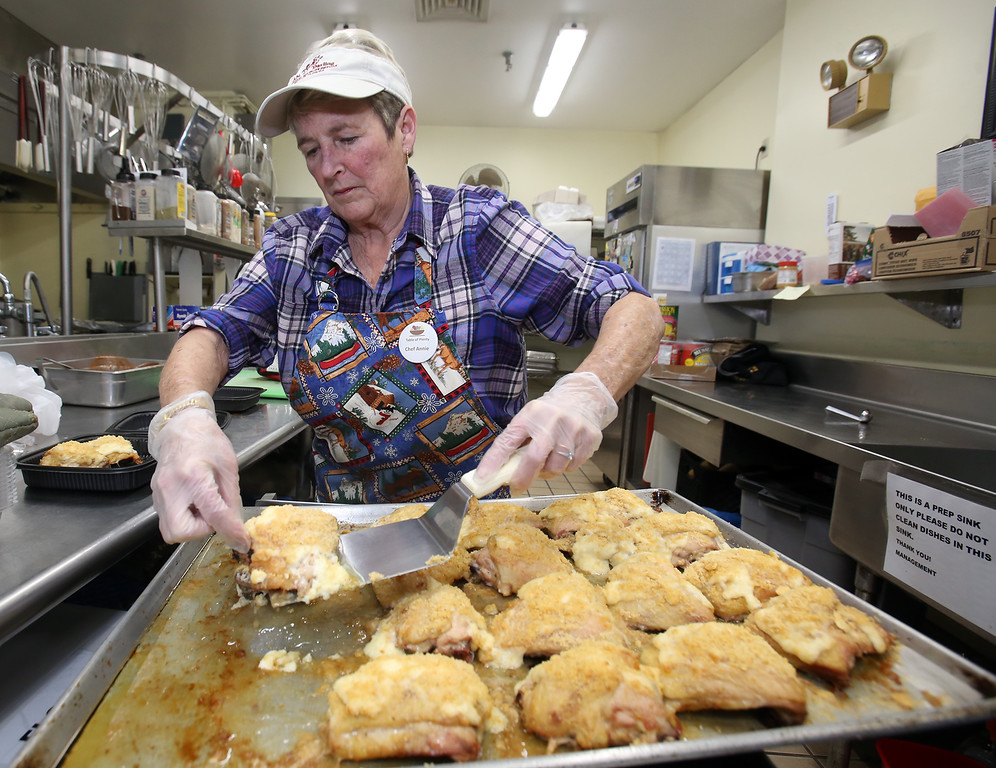 . Table of Plenty volunteers prepare meal at Chelmsford Senior Center. Chef Annie Pelley of Chelmsford places servings of Parmesan Crusted Chicken into containers for families served by My Father\'s House in Chelmsford. (SUN/Julia Malakie)