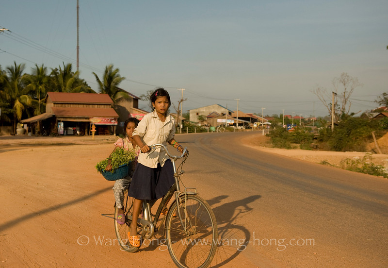 Girls on bike in a small town in North Cambodia, 30km from Preah Vihear