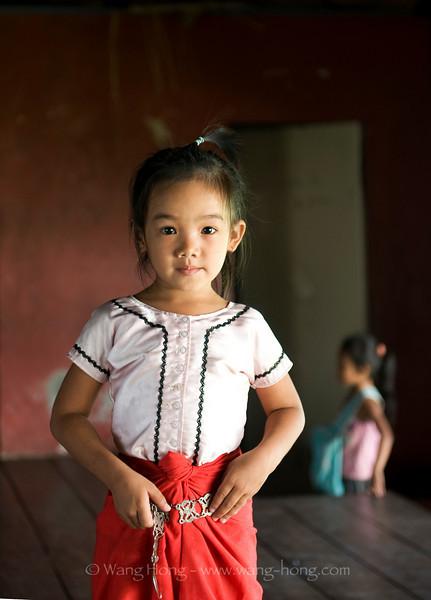 Little girl learning classic Kmer dance at Apsara Art Association in Phnom Penh - putting on her skirt and belt.