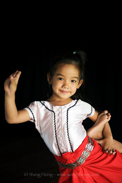 Little girl learning classic Kmer dance at Apsara Art Association in Phnom Penh - posing for picture.