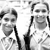 Two school girls walking hand in hand on train tracks near Nuwara Eliya train station.