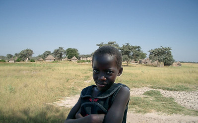 This pretty young girl's village can be seen across the field in the background.  ©Gerald Diamond All rights reserved