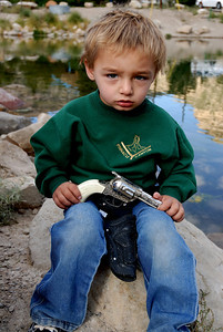 David Openshaw (4) of Price plays with toy gun while parents fish at Gigliotti Pond.  By Brent Stettler, Utah Division of Wildlife Resources, in fall 2007